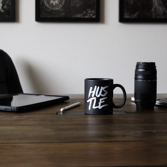 "desk set up with a mug that says ""hustle"" on it, along with a tablet, thermos and pen"