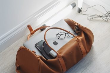 leather travel duffel bag with mac laptop and apple iPhone